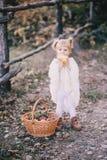 雨披的小女孩吃黄色水多的梨的 免版税库存照片