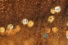 雨水抽象滴在玻璃棕色和橙色颜色的 免版税库存图片