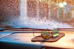 雨珠和湿气在汽车` s朝向玻璃与被弄脏的太阳 库存图片
