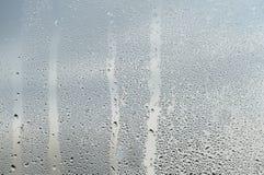 雨珠和水奔跑在一块玻璃窗单块玻璃 免版税库存图片