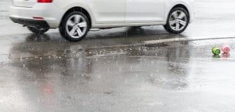 雨珠在有一辆移动的汽车和玩具的一条街道上落 免版税库存照片