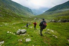 雨衣的远足者在山 免版税库存照片