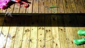 雨钥匙-一个湿长木凳和地板与孩子上色伞和绿色橡胶雨靴和杉木针 免版税库存图片
