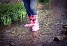雨靴在春天小河 免版税图库摄影