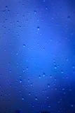 雨水滴在一块玻璃的在蓝色背景 免版税库存图片
