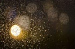雨水滴在窗口和bokeh的 库存照片