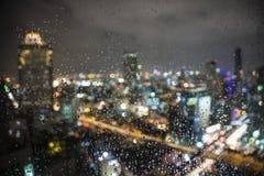 雨水滴在窗口的与迷离city& x27; s夜光后面 库存图片
