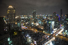 雨水滴在窗口的与迷离city& x27; s夜光后面 免版税图库摄影
