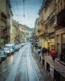 雨水滴在玻璃背景的 街道在焦点外面的Bokeh光 秋天抽象背景 免版税库存照片