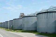 雨水存贮的被镀锌的钢筒仓在温室附近的 免版税库存图片