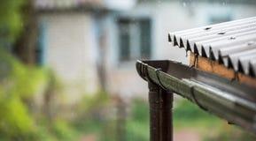 雨从屋顶落入排水管 免版税图库摄影