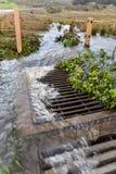 暴雨水流动入流失在路附近 免版税库存照片