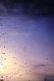 雨水雨/水滴在玻璃的有天空室外背景w 库存照片