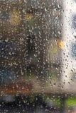 雨水雨/水滴在玻璃的有室外背景 库存照片