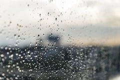 雨水雨/水滴在玻璃的有室外背景 免版税图库摄影