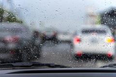雨水雨/水滴在玻璃的用在路的交通堵塞,  免版税库存照片