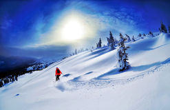 滑雪下坡在高山的滑雪者反对日落 免版税库存图片