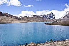 雪与蓝色湖的加盖的山 库存照片