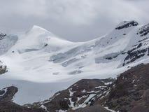 雪与暴风云的加盖的山峰 免版税库存照片