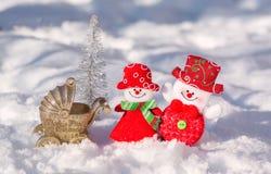 雪人丈夫和妻子是美妙地穿戴的微笑反对一棵发光的圣诞树的背景与婴儿推车的 免版税库存图片