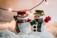 雪人和电灯泡在堆雪中站立在沈默夜、圣诞快乐和新年好晚上 免版税图库摄影