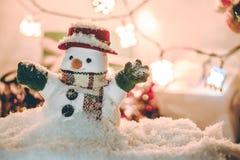 雪人和电灯泡在堆雪中站立在沈默晚上,打开充满希望的人和幸福在圣诞快乐和机会 免版税库存照片