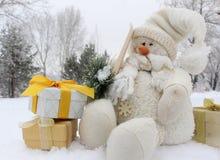 雪人和礼物盒在雪在冬天森林里 库存照片