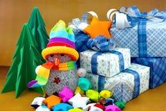 雪人和礼物盒有圣诞树和小星纸的 免版税库存照片