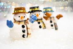 雪人在降雪、圣诞快乐和新年快乐概念站立 库存图片