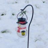 雪人在雪的圣诞灯 免版税库存图片