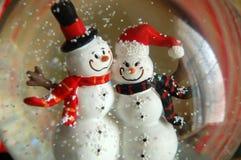 雪人夫妇在雪地球的 库存照片