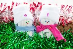 雪人夫妇从白色袜子的在帽子和桃红色围巾 库存照片