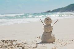 雪人由沙子制成在热带温暖的海的背景 免版税库存照片