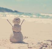 雪人由沙子制成在热带温暖的海的背景 库存图片