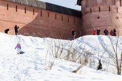 雪倾斜的游人在修道院附近墙壁  免版税库存照片