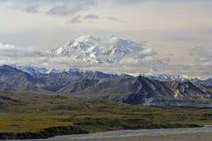 雪偷看通过云彩的加盖的山 免版税库存照片