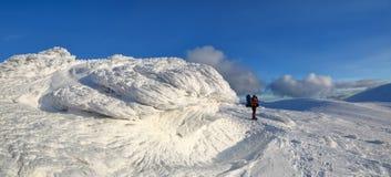 雪全景用织地不很细,结冰的,神秘的稀奇的形状的石头,滑雪服的一个人加盖了山 库存照片
