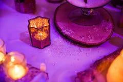 雪剥落婚礼与蜡烛的表装饰在紫色光 库存照片
