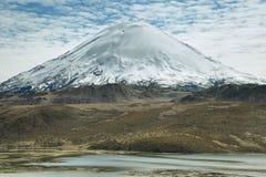 雪加盖了在湖反映的高山Chungara 库存照片