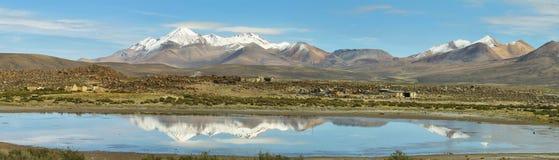 雪加盖了在湖反映的高山Chungara 免版税库存图片