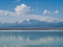 雪加盖了在蓝色湖反映的山 免版税库存图片