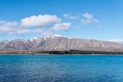 雪加盖的山和蓝色特卡波湖 库存图片