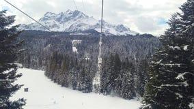 雪加盖的山缆绳推车 库存图片