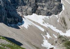 雪和冗长的句子在一个高山峰顶下 免版税库存照片