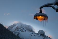 雪和冰柱报道了琥珀色的lightpost反对风背景  免版税库存图片