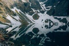 雪和山的神秘的反射在恰尔内Staw黑色池塘中,塔特拉山脉,波兰水  免版税库存照片