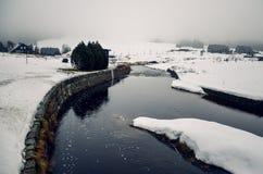 雪和河盖的Jizerka村庄在冬天 图库摄影