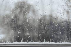 雪和雨在窗口,与警察的恶劣天气背景滴下 库存图片