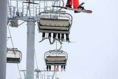滑雪和雪板车手的腿在缆绳升降椅的在多云多雪的冬天山风景关闭 免版税库存图片