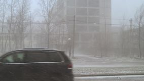 雪和风在城市在的房子背景的春天下午  股票录像
